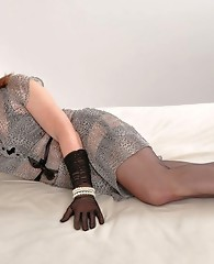 Crossdressing tart dressed in a gorgeous grey dress posing on her big bed.