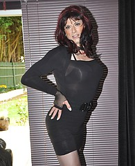 Sexy crossdresser Gloria posing in a short black dress and silky nylon stockings